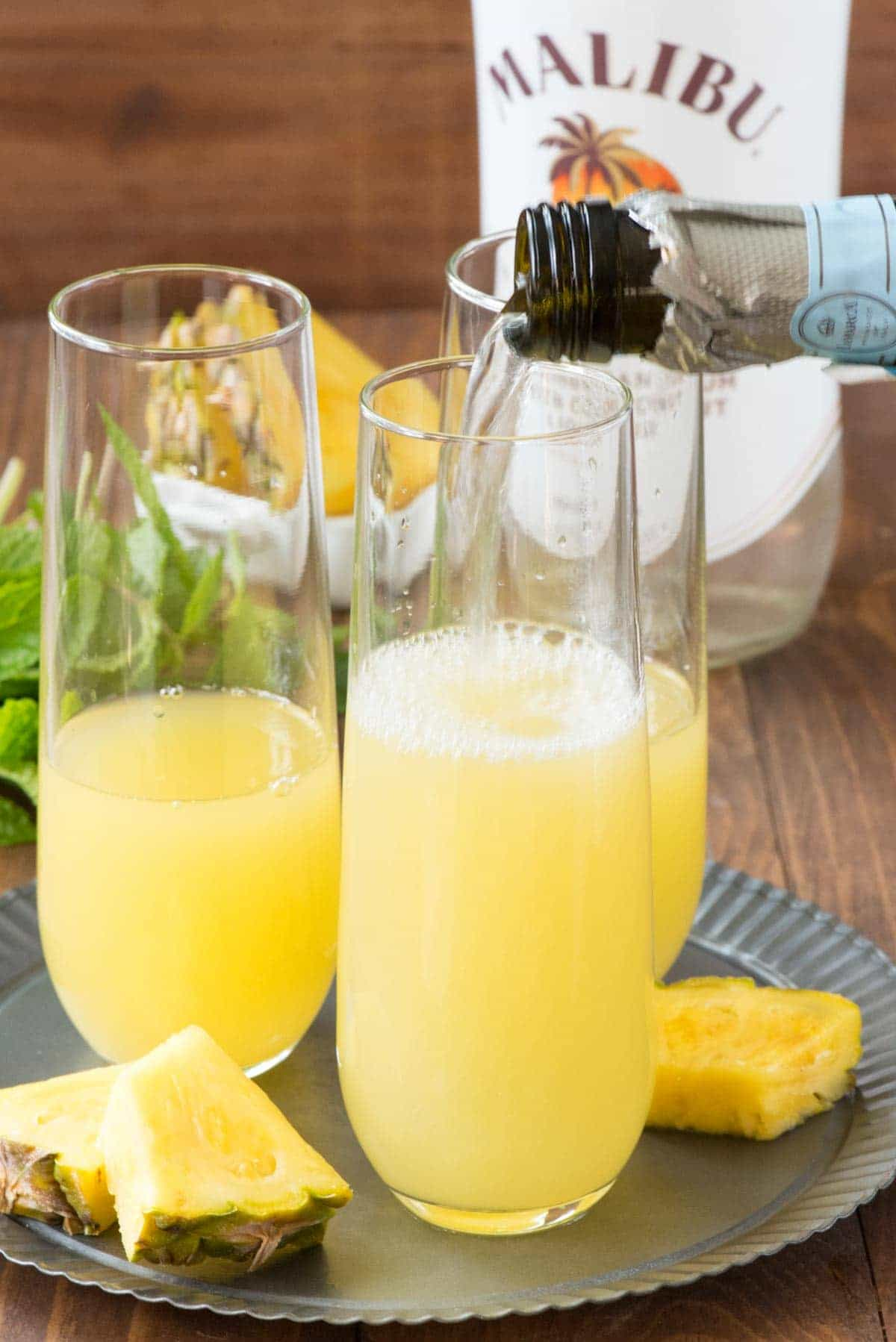 Adding Prosecco into three drinking glasses to make Hawaiian Mimosas .