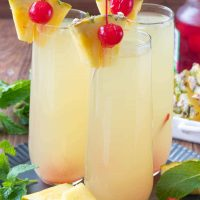Three Hawaiian Mimosas garnished with cherries and sliced pineapple on a plate.