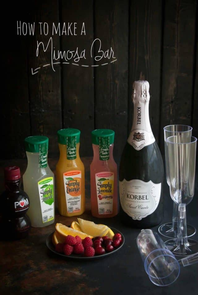 A Mimosa Bar with champagne, simply lemonade, champagne glasses and a plate of cherries, raspberries and sliced oranges.