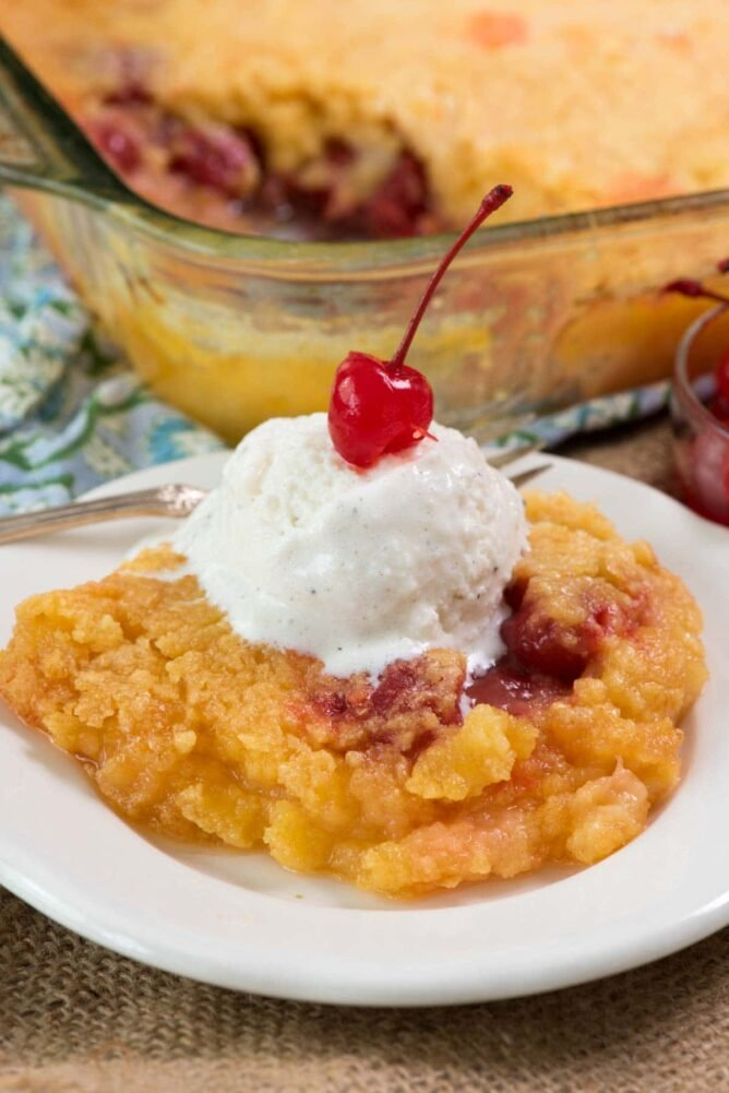 pineapple upside down dump cake on white plate with ice cream and cherry