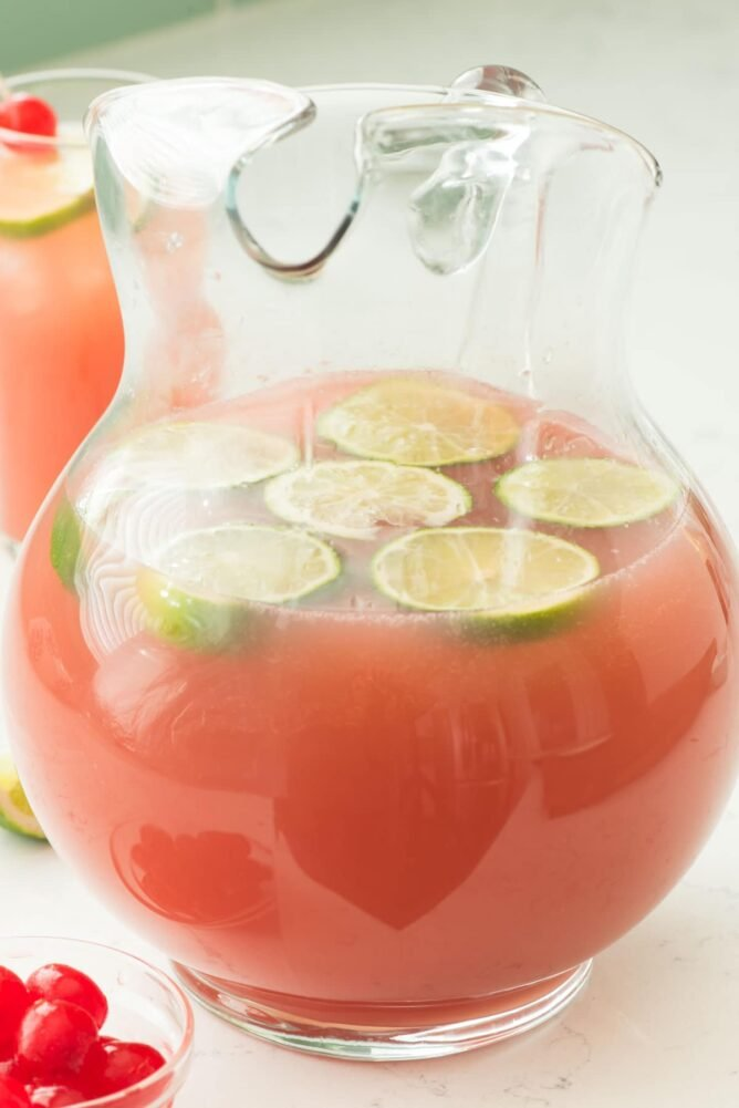 Salty dog punch in a glass pitcher with lime slices