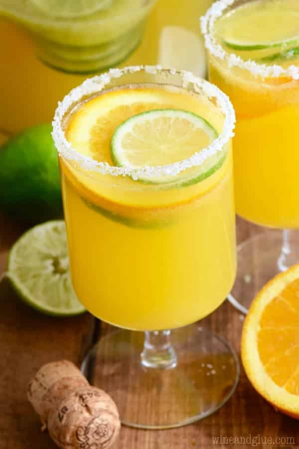 Two Mimosa Margaritas rimmed with salt and garnished with sliced limes and oranges.