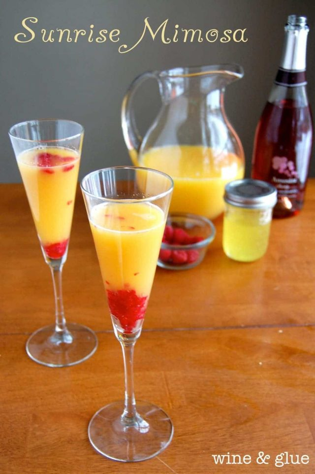 Two glasses of Sunrise Mimosas with a pitcher, champagne and fresh raspberries in the background.