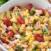 BBQ Chicken Pasta Salad in a white bowl with limes and some cilantro behind it