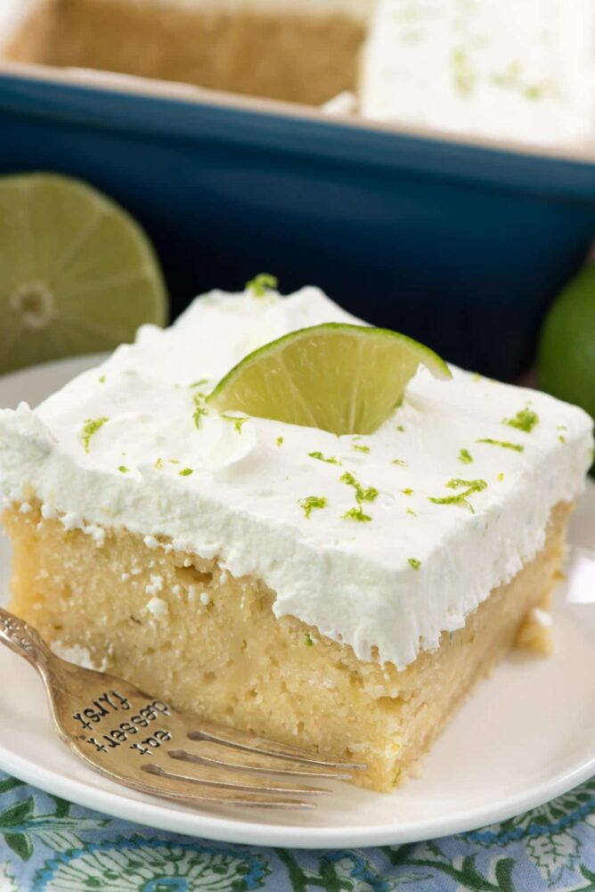 Easy Key Lime Cake from scratch on white plate with fork - this perfect cake recipe is made with key lime juice and then soaked with key lime glaze and topped with fresh whipped cream. It's even lower in added sugar!