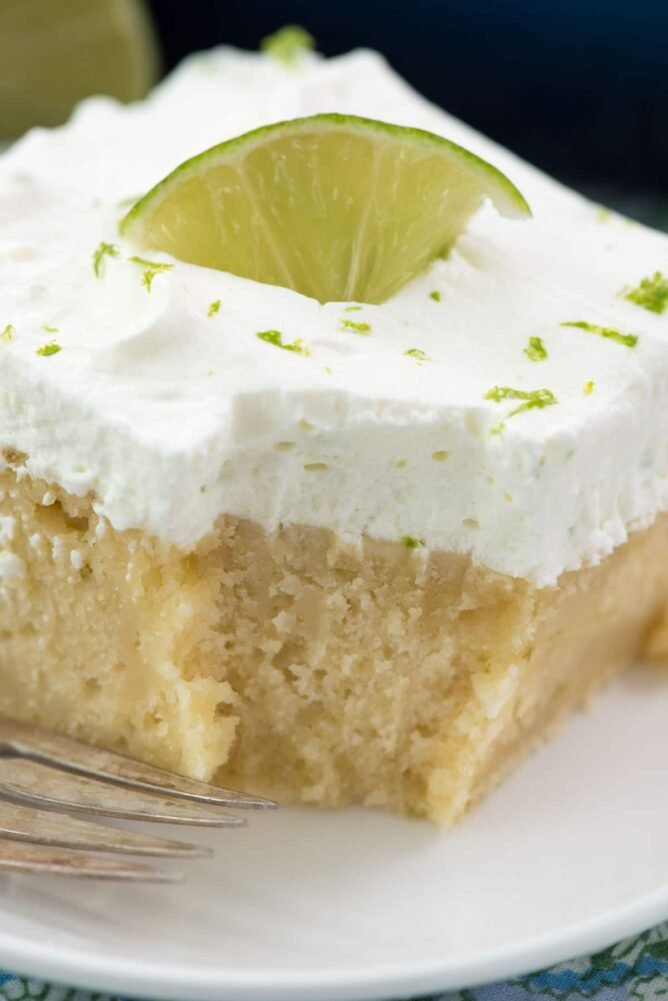 Easy Key Lime Cake from scratch on white plate with bite missing - this perfect cake recipe is made with key lime juice and then soaked with key lime glaze and topped with fresh whipped cream.