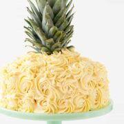 Picture of Pineapple cake with the top of a pineapple on top of the cake A pineapple cake is a frosted 2 layer cake decorated with buttercream icing rosette swirls to make it look like a pineapple! Get the recipe tutorial here!