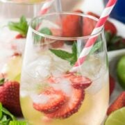2 Clear glass half filled with Strawberry Lime Punch with ice. Strawberries are in the glass and it has some mint and a red and white stripes. Thee are lime slices and mint and strawberries next to the glasses