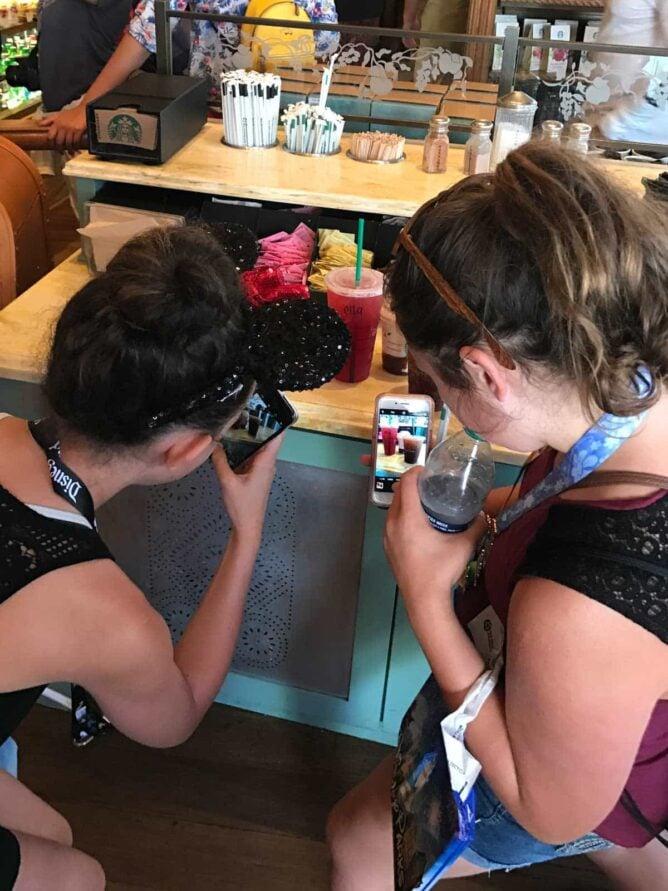 girls taking photos of starbucks drinks in Disneyland Starbucks