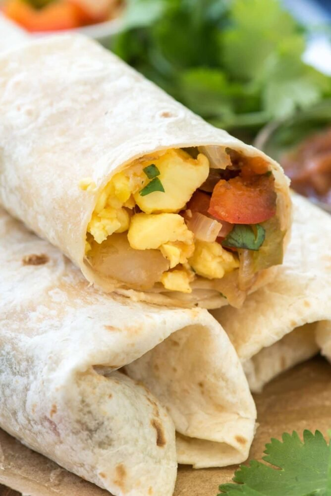Easy Mexican Breakfast Burritos in a stack sliced in half! These semi-homemade breakfast burritos start with a frozen breakfast bowl and have added vegetables and Mexican flavors. These are the PERFECT breakfast for on the go!