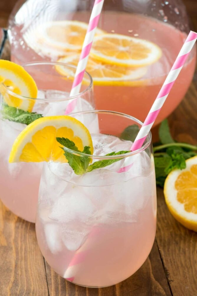 Pink Rose Lemonade in glass with lemon and mint and striped straw