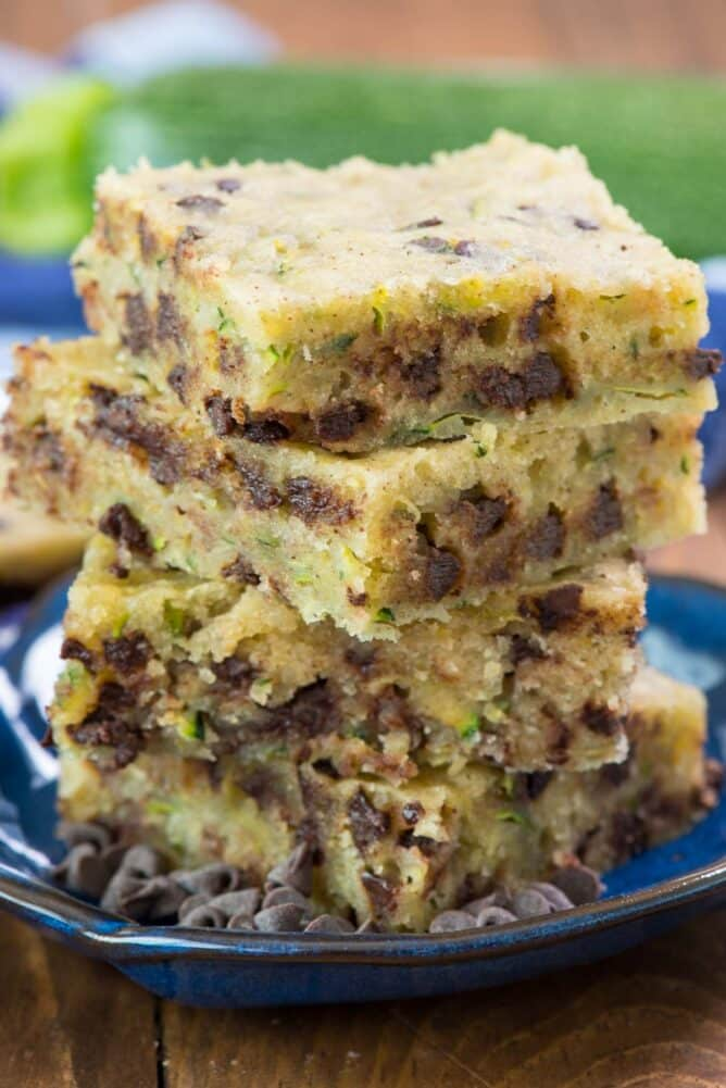 Chocolate Chip Zucchini Bars in stack on blue plate- this easy one bowl zucchini bar recipe isn't quite a cookie or a cake but it's a delicious soft and sweet dessert full of zucchini and chocolate!