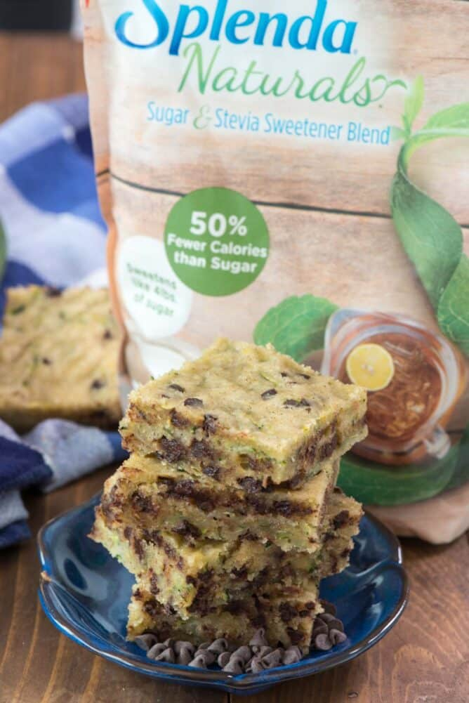 Easy one bowl chocolate chip zucchini bars in a stack on blue plate with splenda bag
