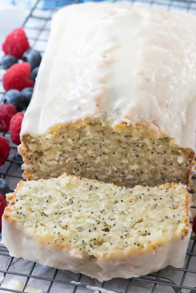 Almond Poppyseed Loaf Cake on rack with one slice