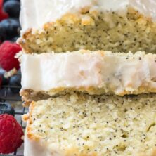 sliced almond poppyseed cake with frosting on rack