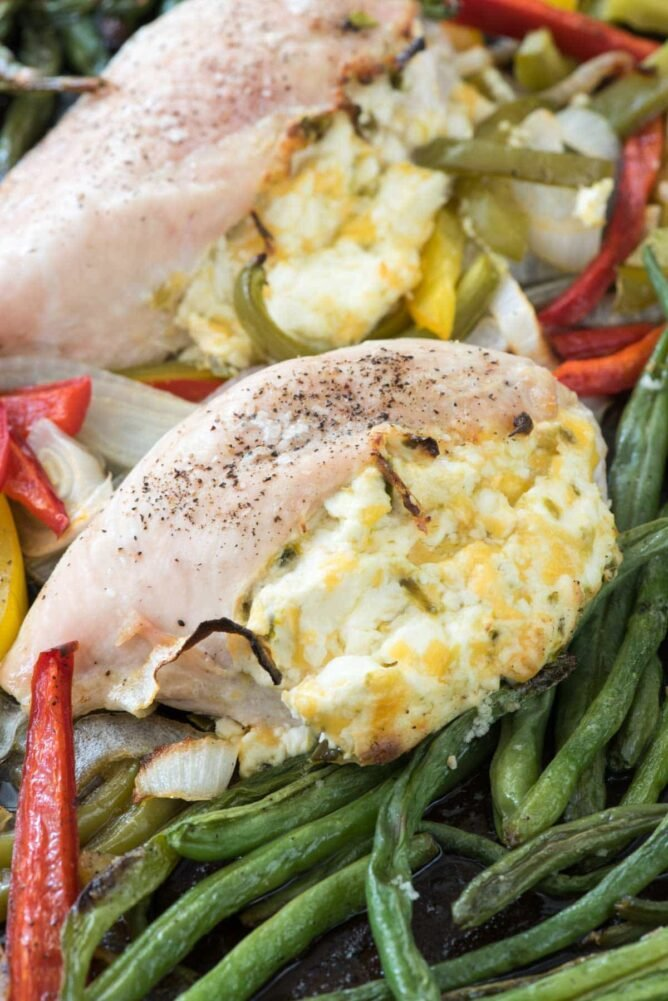 Jalapeño Popper Sheet Pan Chicken close up of chicken stuffed with filling on green beans