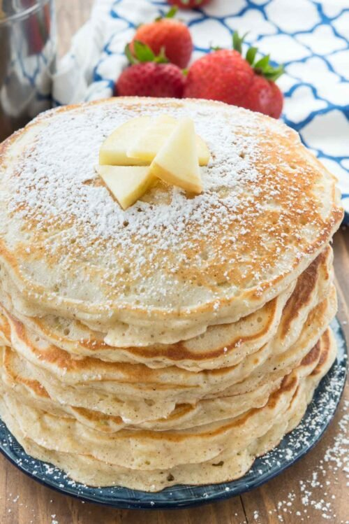 Stack of pancakes with powdered sugar and butter on blue plate with strawberries and a blue and white napkin