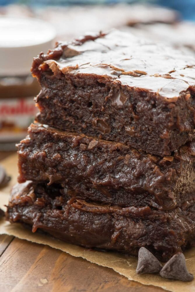 These are the BEST NUTELLA BROWNIES EVER in a stack on parchment paper