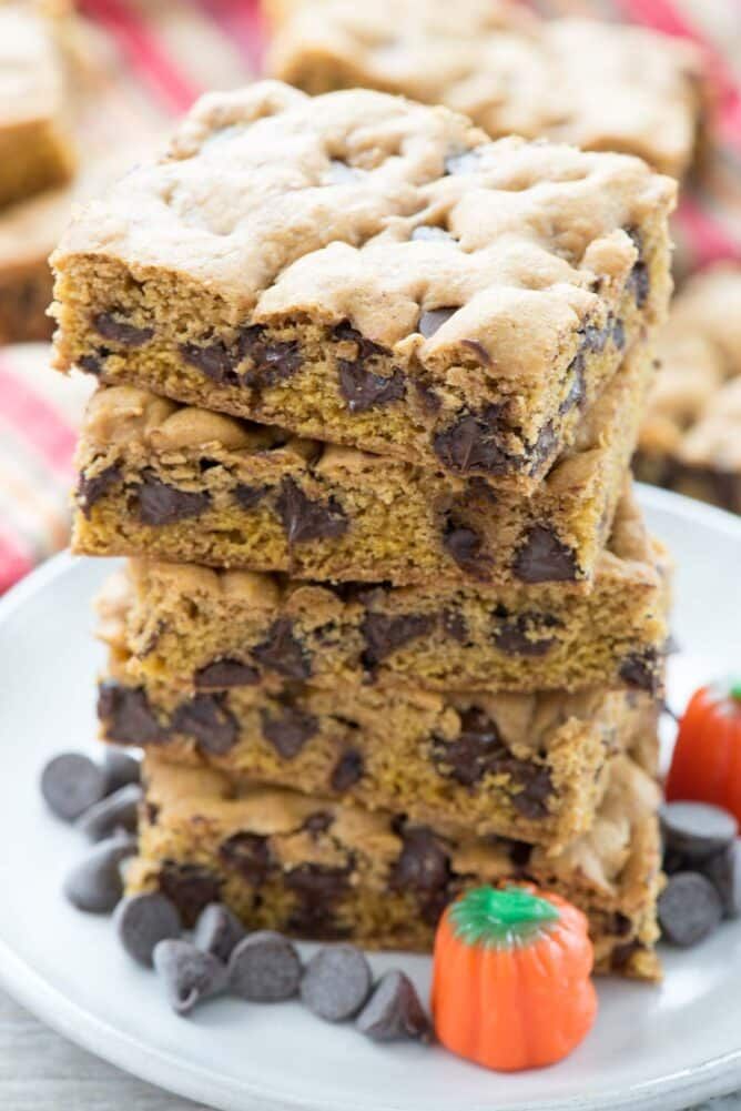 The BEST Pumpkin Blondie Recipe in a stack on white plate with chocolate chips