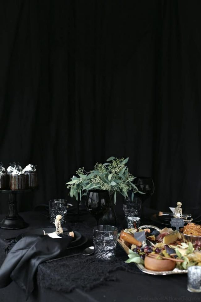 Halloween Themed Dinner  with black table cloth and lots of greens in a vase
