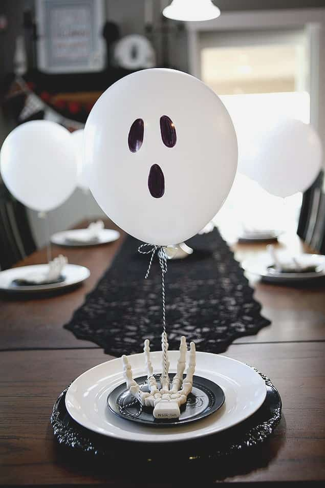 Balloon Ghost Table Setting with ghost balloons and a hand on top of a big white plate and a small black plate
