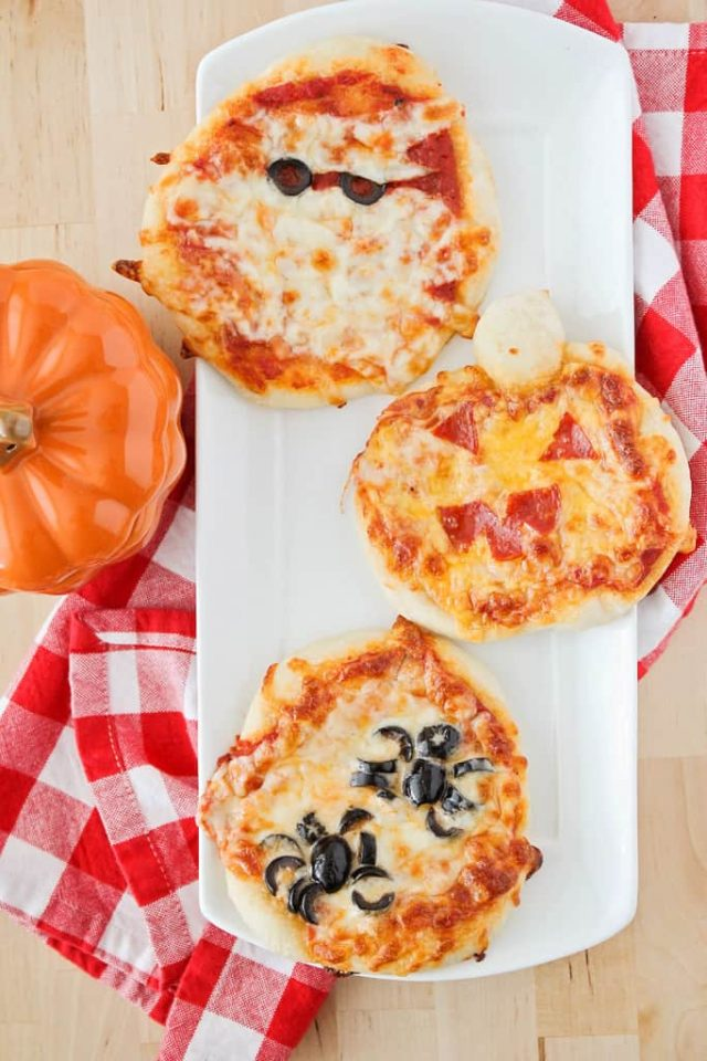 Halloween Mini Pizzas with olive eyes on one and pepperoni eyes and mount on one and black olive spider on the other