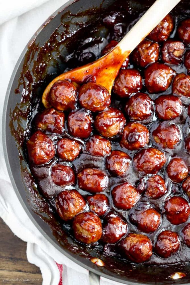Cranberry bbq meatballs in a pot with a spoon.