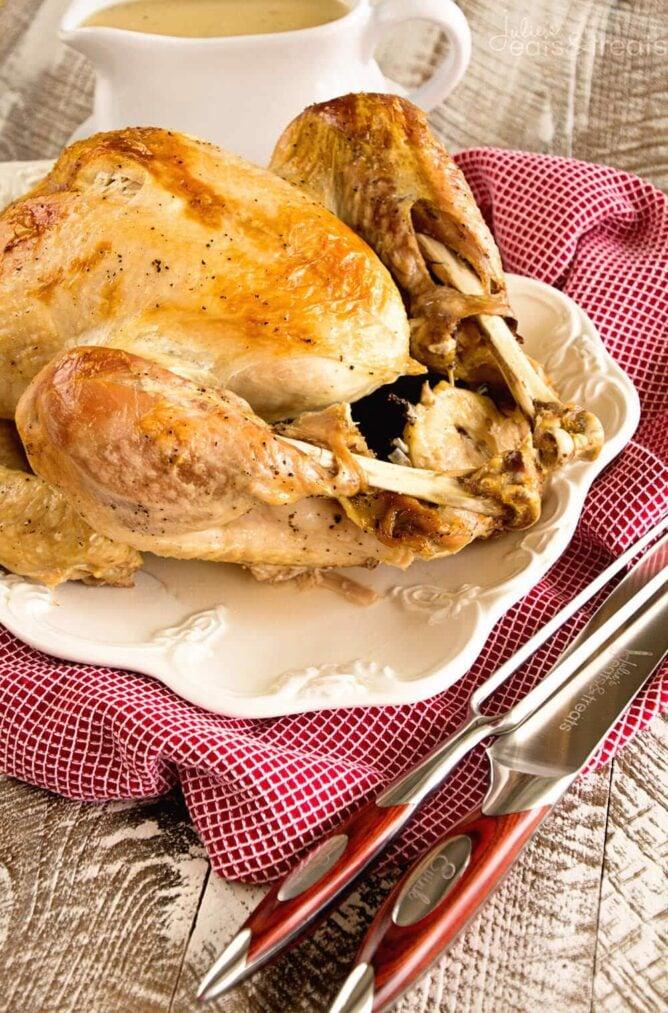 Crockpot make ahead whole turkey on a platter with gravy.