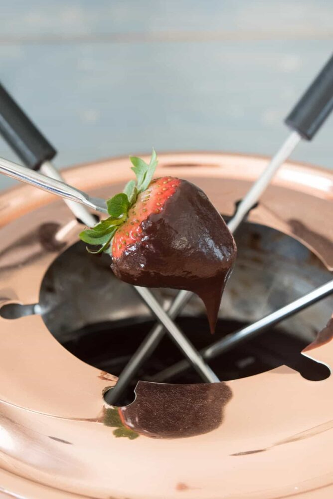 Chocolate dipped nutella fondue strawberries and a fondue pot with forks.