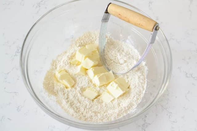 butter and flour in bowl with pastry cutter