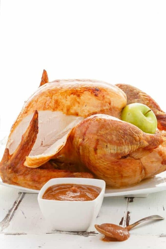 Roasted apple butter whole turkey missing a slice on a white platter.