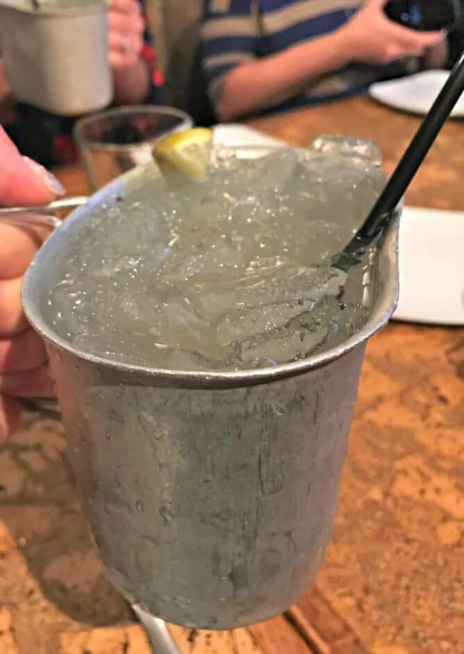 a metal bucket with ice and a drink sitting on a table