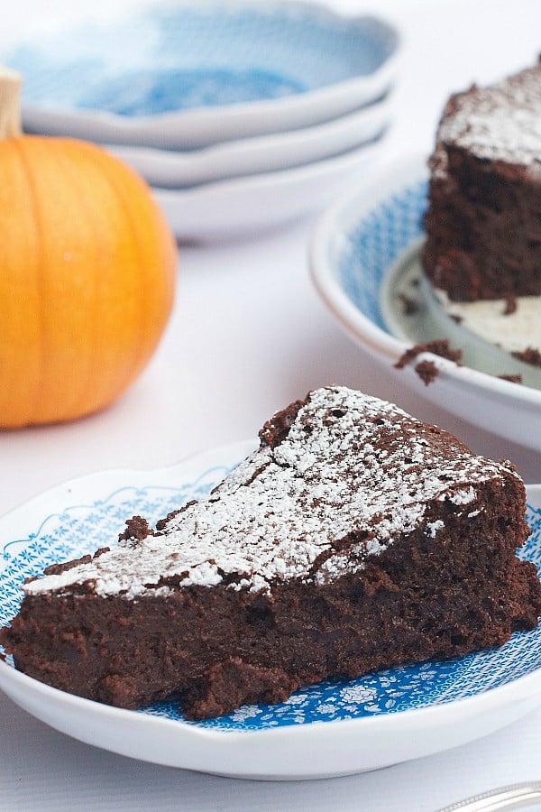 Pumpkin spice flourless chocolate cake slice on a blue plate.