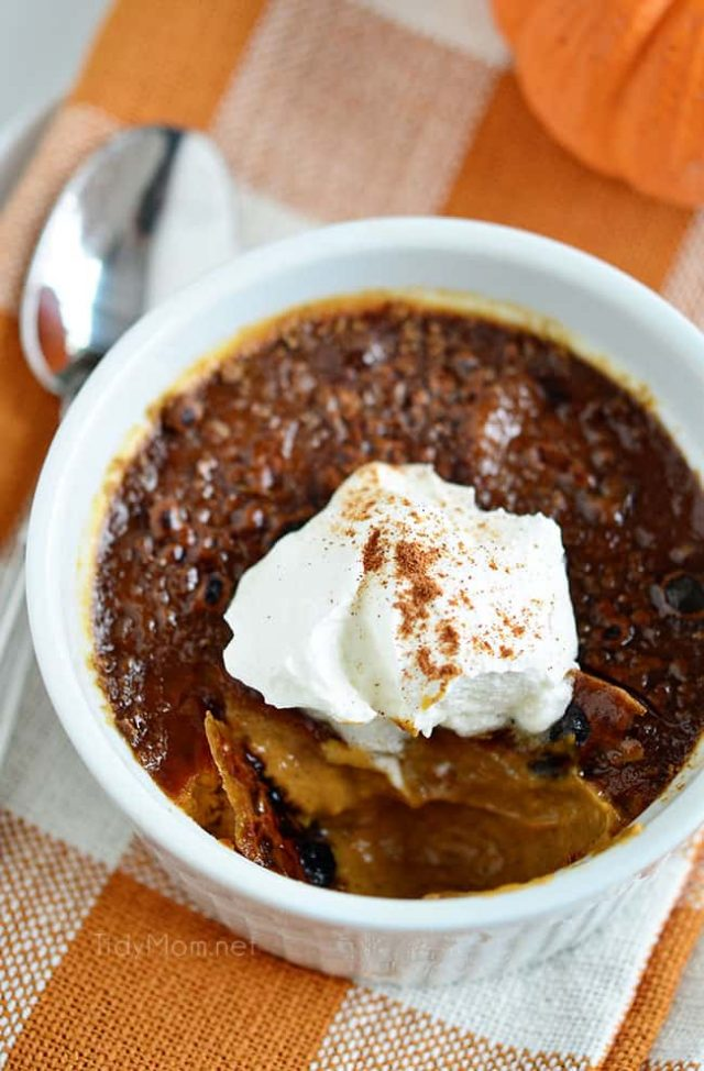 Pumpkin creme brulee in a white dish with a dollop of whipped cream.