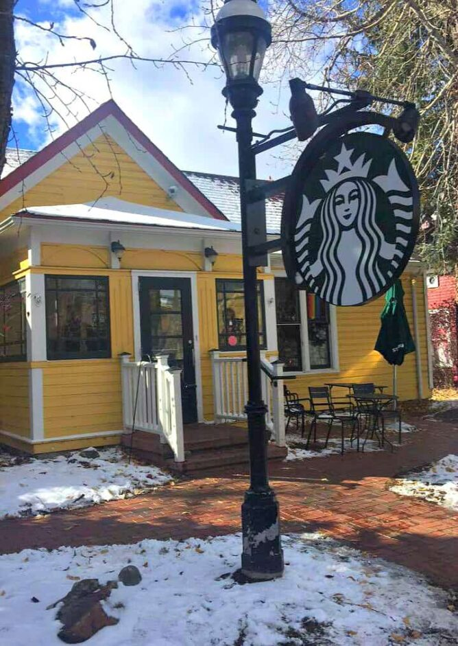 Picture of Starbucks logo and a small yellow starbucks  location in the back