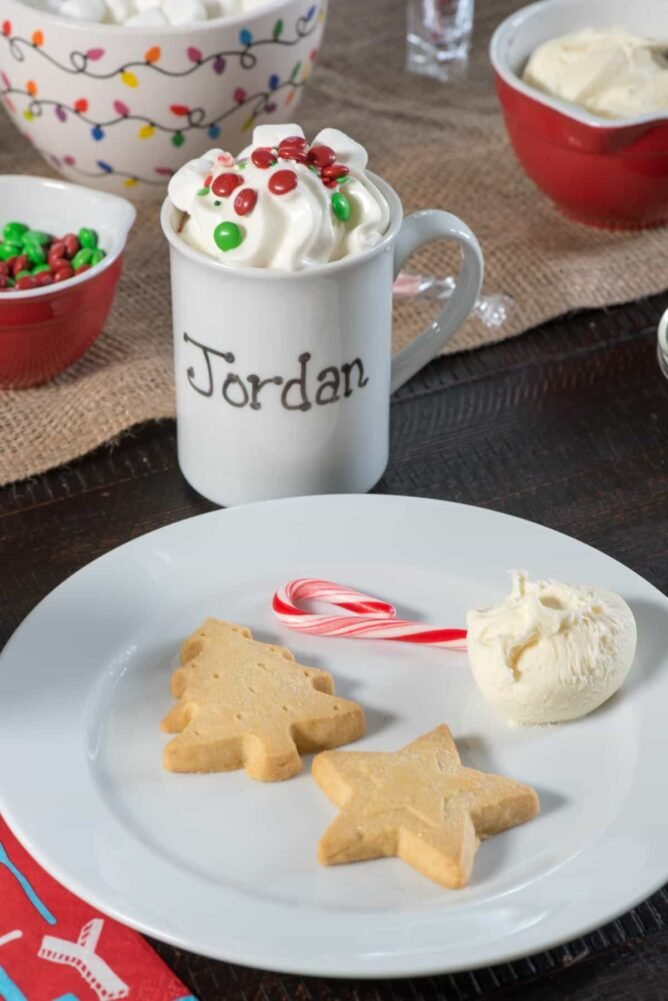 Christmas cookies on a white plate with a mug in the background