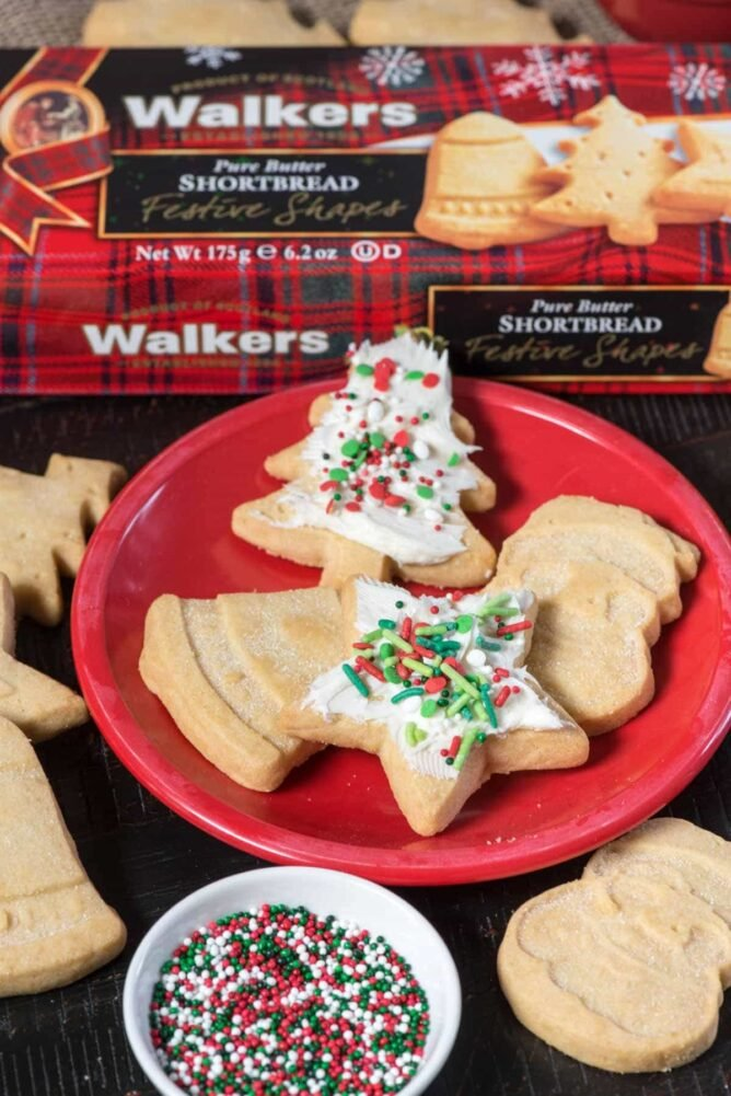 Christmas cookies on a red plate with Walkers Shortbread cookies in the background