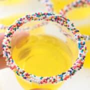 Hand holding lemon jello shot with sprinkles