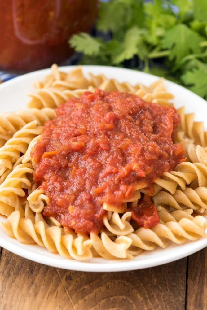 tomato sauce on pasta on a white plate