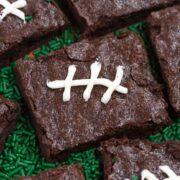 brownies iced like footballs flat on green plate