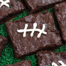 brownies iced like footballs flat on green plate
