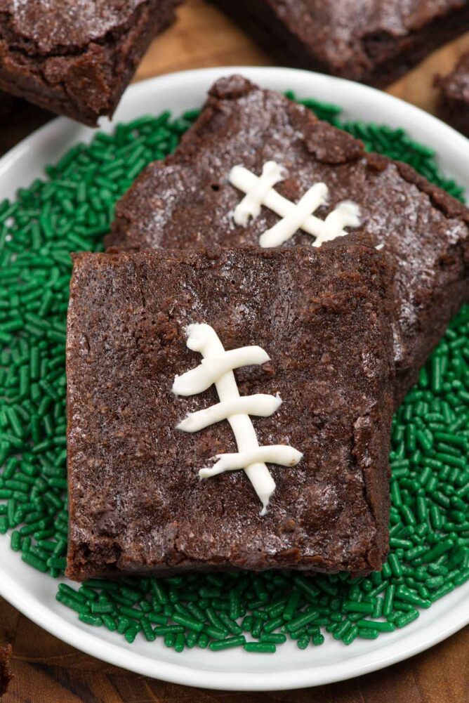 Football brownies surrounded by green sprinkles on a white plate