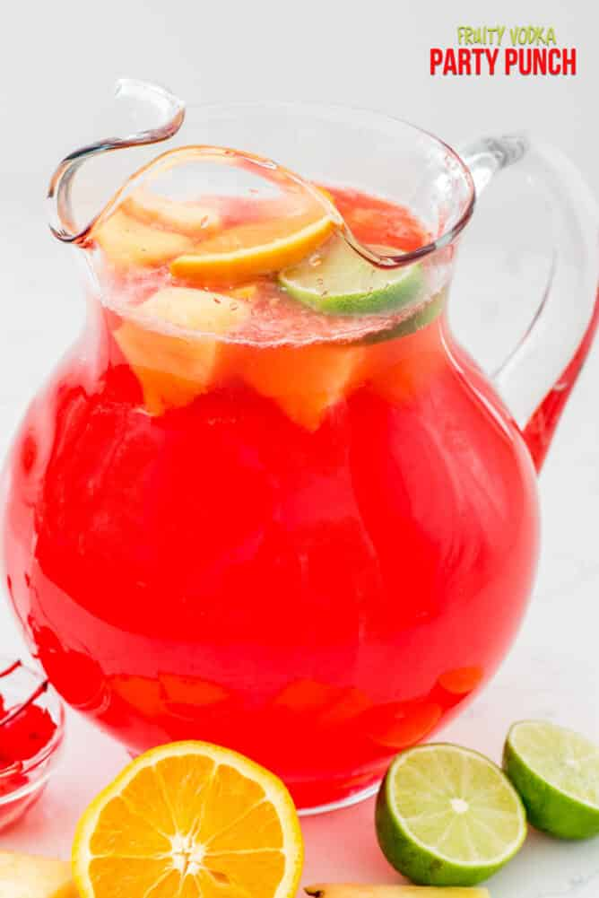 red vodka punch in pitcher with lemons and limes around the pitcher