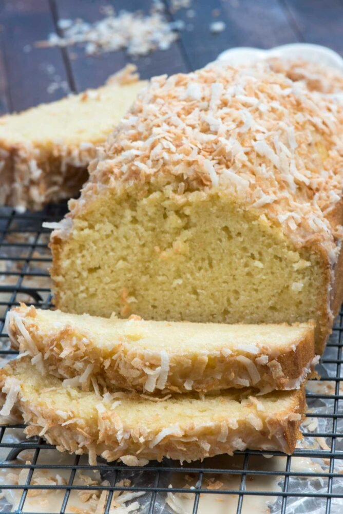 sliced coconut pound cake on a wire stand
