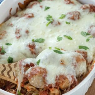 Casserole dish with spoon holding up meatballs and cheese
