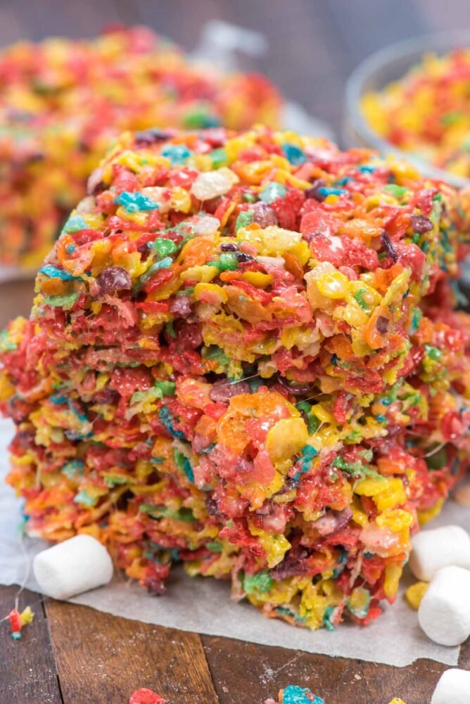 stack of fruity pebble kristpie treats on parchment paper