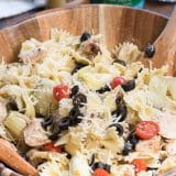 pasta salad in wood bowl with dressing bottle
