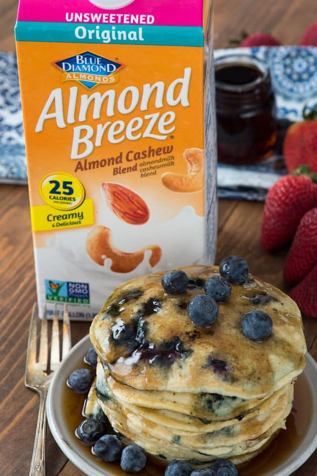 stack of blueberry pancakes on white plate with almond breeze container
