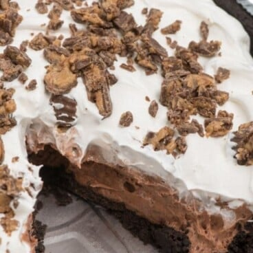 pie with cool whip and peanut butter cups on top with slice missing