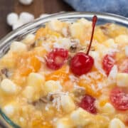 Tropical Ambrosia Salad in a glass bowl with writing